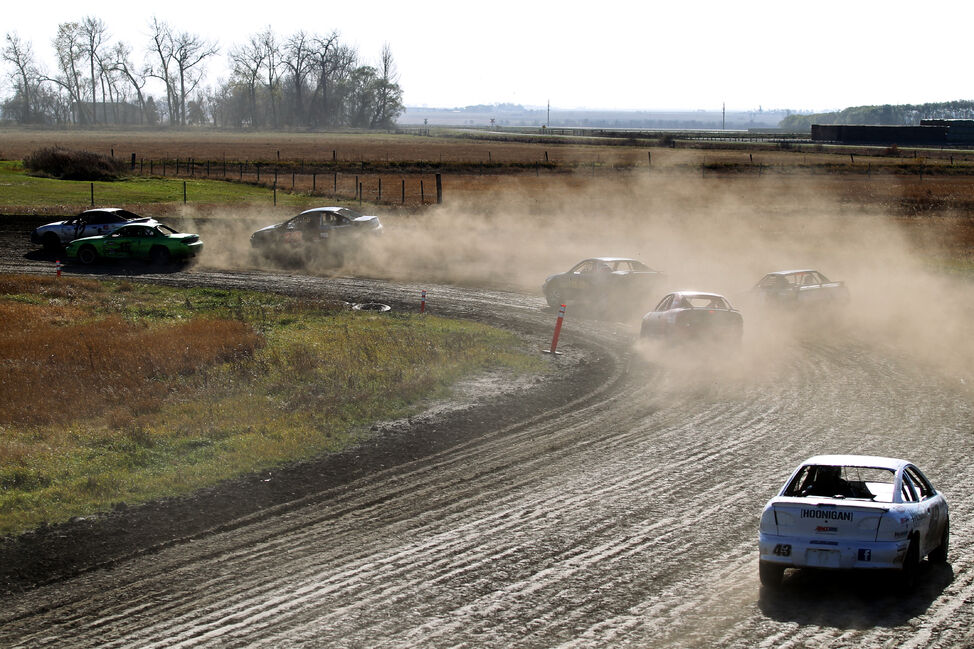 Cars slide through the dirt, stirring up dust as they round a corner during the championship heat.
