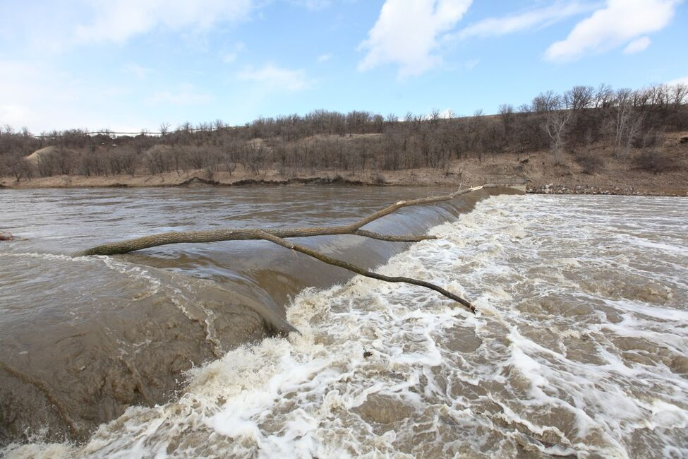 Water from the Souris River rages over the dam in Wawanesa on Monday.