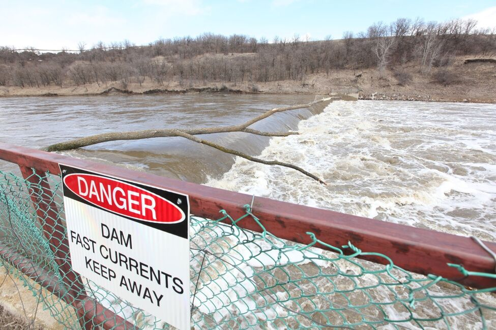 Water from the swollen Souris River rages over the dam in Wawanesa on Monday.