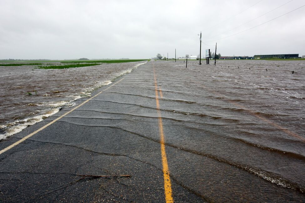 Overland flooding spills over Sandison Road near the Brandon Municipal Airport on Sunday after rain fell almost non-stop throughout the weekend. The airport was closed due to the flooding.