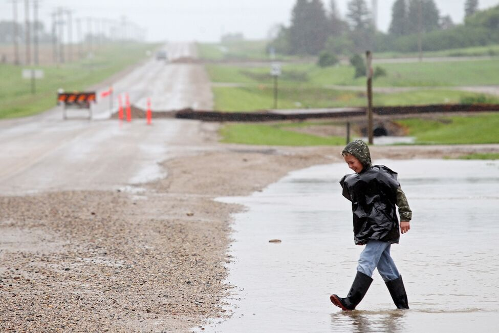 A young boy plays in the flood water adjacent to Highway 256 in the village of Cromer in southwestern Manitoba on Sunday after incessant rainfall over the weekend caused flooding forcing the evacuation of approximately 30 residents.