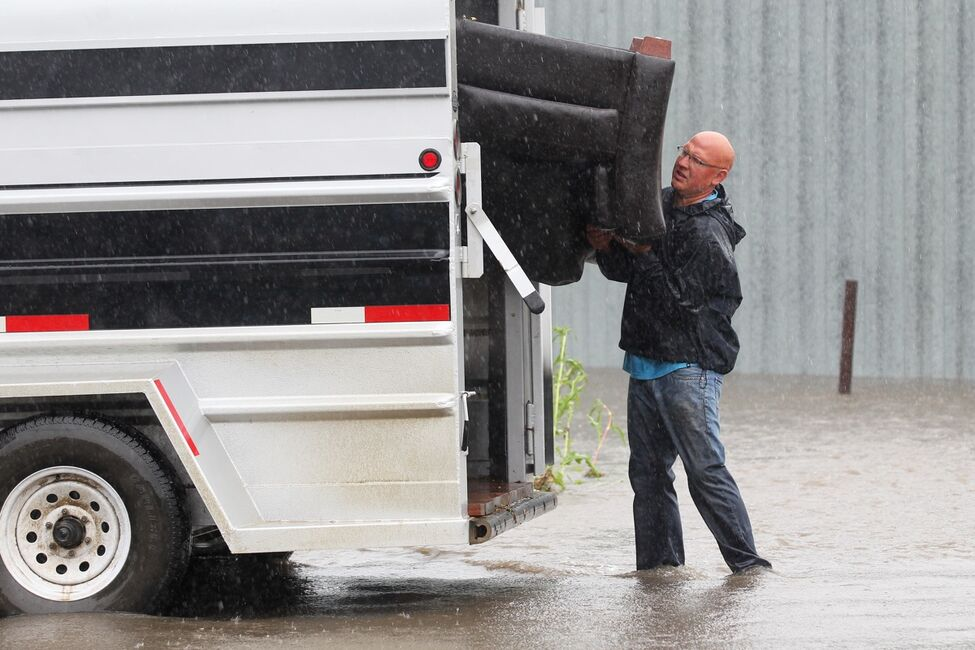 Greg Baerg loads a couch into a trailer on Sunday after the home he and his wife Amy live in in the village of Cromer in southwestern Manitoba flooded due to excessive rainfall over the weekend. The Baerg's are from Alberta but are living in Cromer while working in the area.
