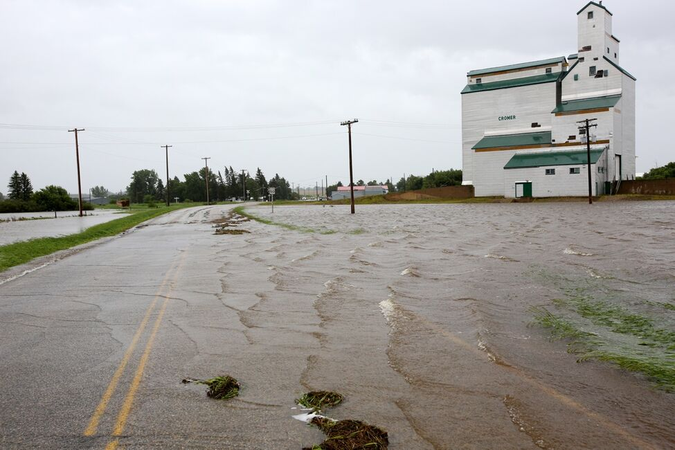Water pours over Highway 256 just north of the village of Cromer in southwestern Manitoba on Sunday after incessant rainfall over the weekend caused flooding forcing the evacuation of approximately 30 residents.