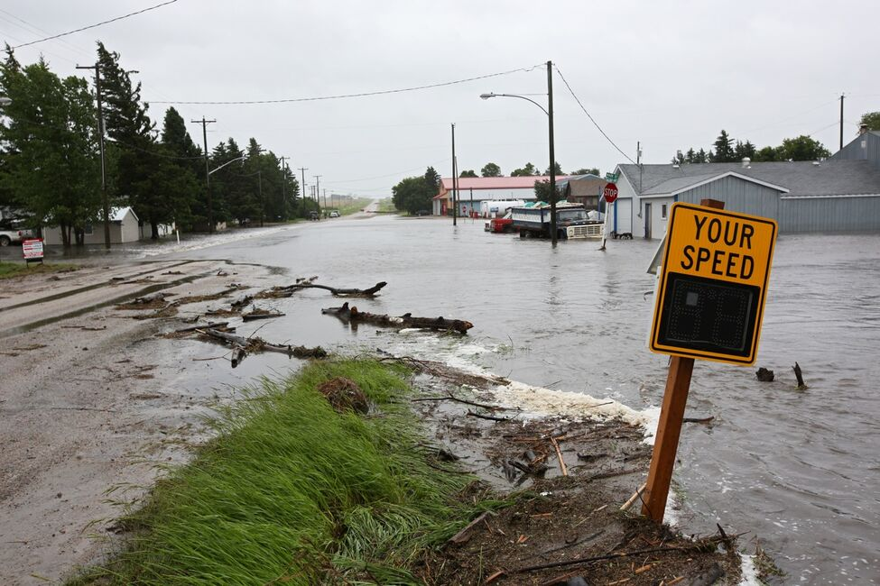 Water pours over Highway 256 in the village of Cromer in southwestern Manitoba on Sunday after incessant rainfall over the weekend caused flooding forcing the evacuation of approximately 30 residents.