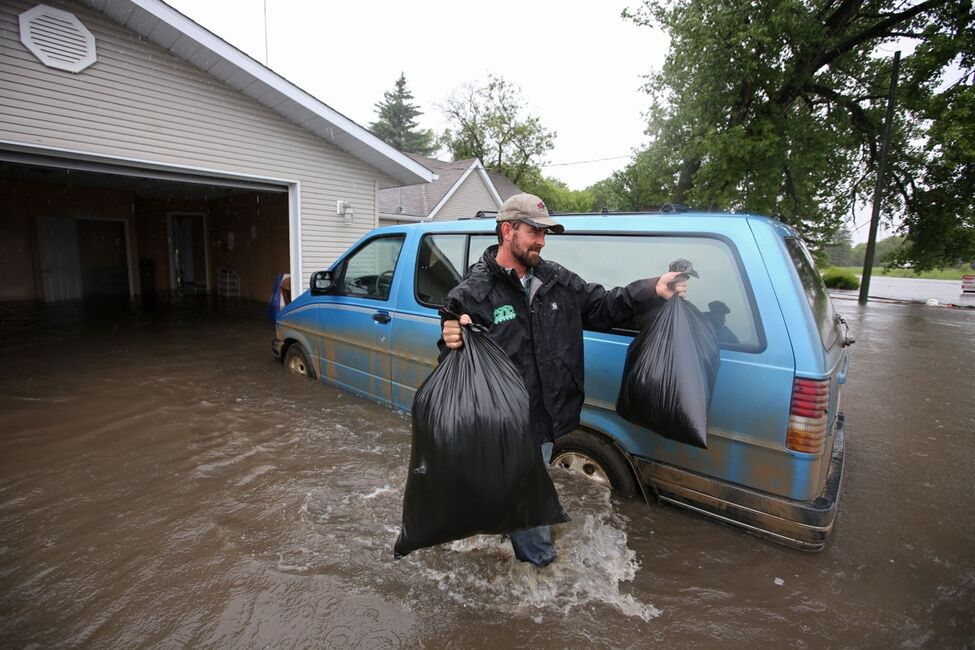 Ivan Penner carries belongings from the flooded home of Greg and Amy Baerg to a waiting trailer in the village of Cromer in southwestern Manitoba on Sunday after flood water inundated several homes in the small community and forced the evacuation of approximately 30 residents.