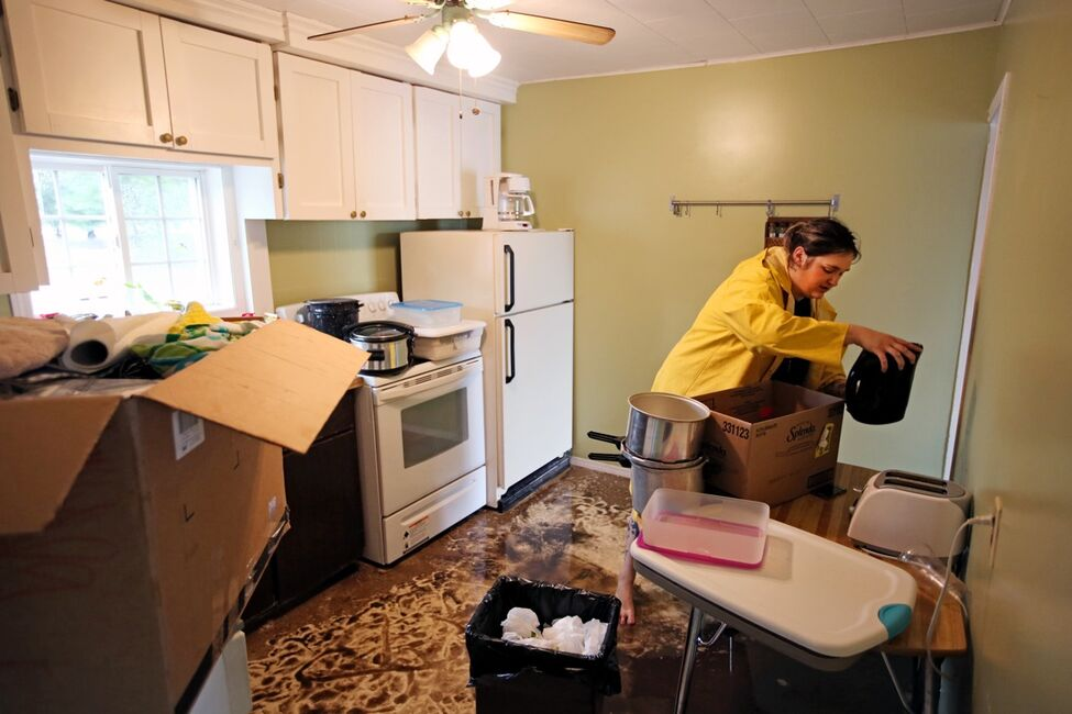 Ashley Feldman packs up belongings in the home of her neighbours Greg and Amy Baerg on Sunday after the home in the village of Cromer in southwestern Manitoba was flooded due to excessive rainfall over the weekend. Several homes in the small community were flooded and approximately 30 residents were evacuated.