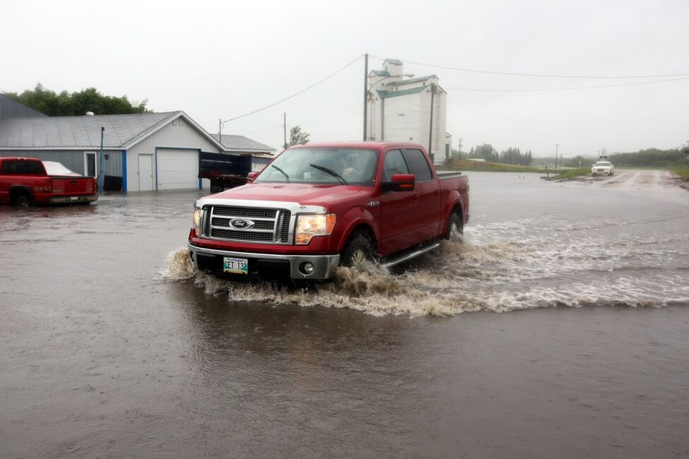 A truck makes its way through floodwaters covering Highway 256 in the village of Cromer in southwestern Manitoba on Sunday after incessant rainfall over the weekend caused flooding forcing the evacuation of approximately 30 residents.
