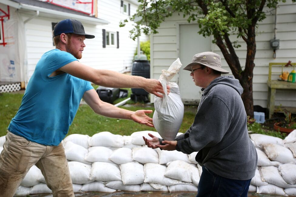 Blair Bartel passes a sandbag to Jayson Brockman while the two volunteers help build a sandbag dike around homes in the town of Reston in southwestern Manitoba on Sunday after incessant rainfall creating overland flooding in the community. Reston was hit hard by flooding just over a year ago.