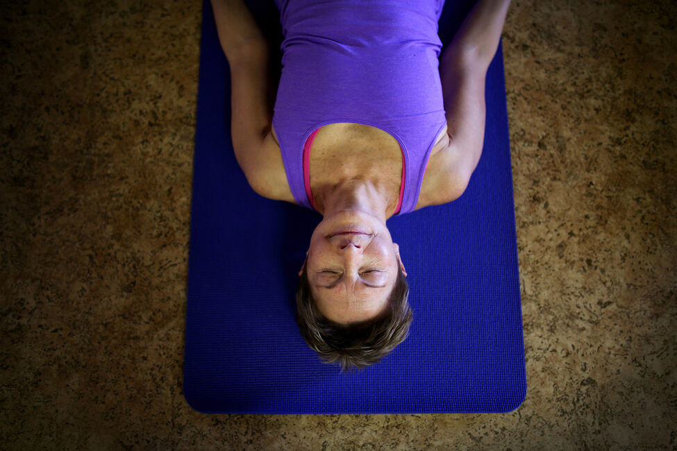 Lil Martin lies on her yoga mat between poses during a Gentle Vinyasa Flow yoga class at The Zen Zone on 10th Street in Brandon on Monday morning.