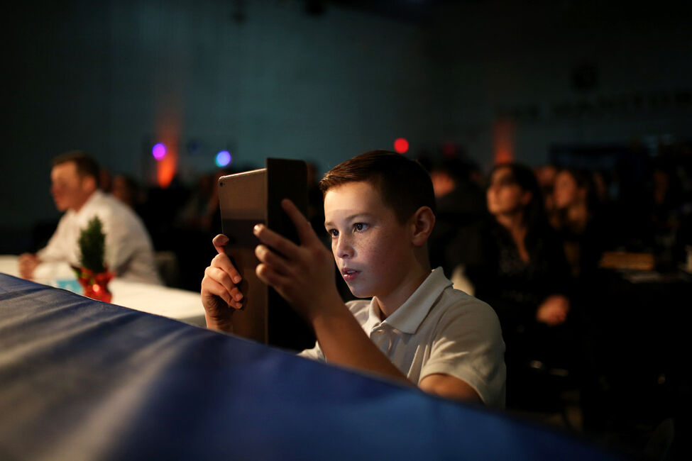 A young boy records a bout from ring side.
