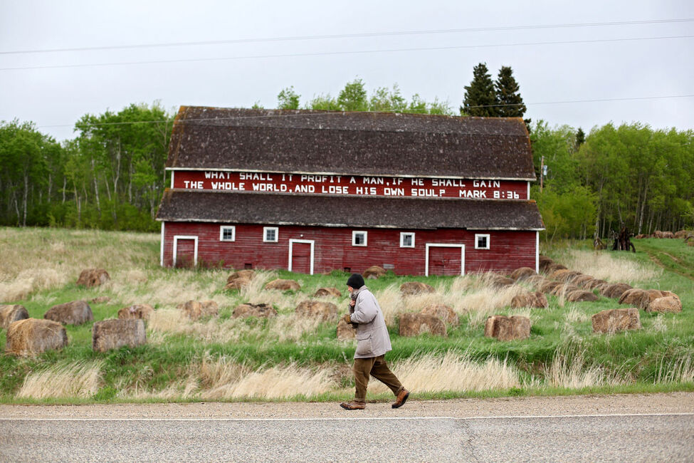 Clare cinches his jacket to keep out the cold as he begins his walk north to Erickson on Highway 10 on a cool day in May. The bible scripture was painted on his barn more than twenty years ago and is a common sight for travellers on Highway 10.