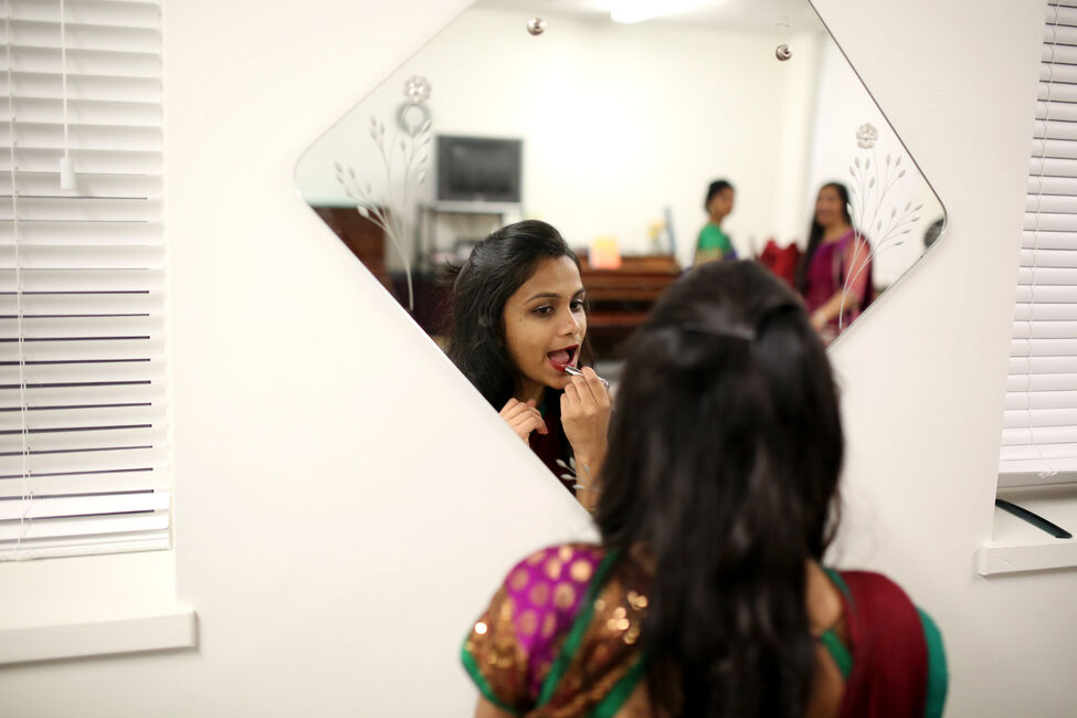 Aesha Patel is reflected in a mirror while applying lipstick prior to performing during the Eid-Diwali-Christmas celebration.