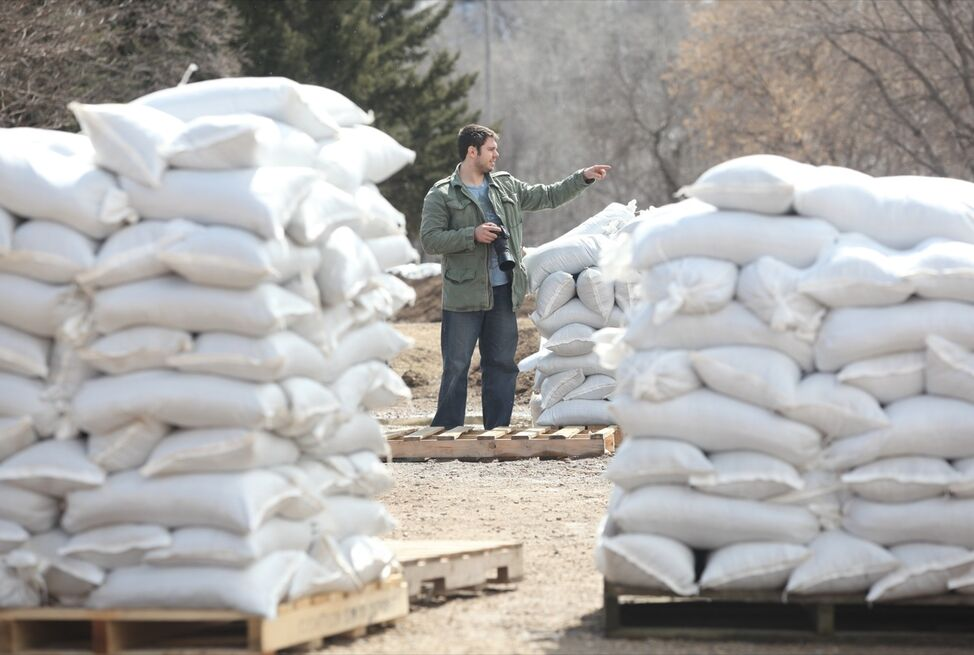 Colin Blyth of Brandon is framed by pallets of sandbags as he surveys the Souris River level at the edge of the Wawanesa School parking lot in Wawanesa with friend Mike Farquhar (not shown) on Monday. Blyth and Farquhar are kayakers and were scouting out areas to kayak when the river levels drop. A dike has been built around the Wawanesa school to protect it from flooding.