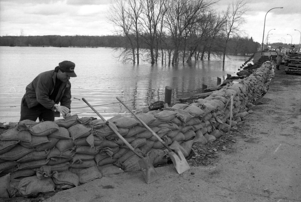 Workers build up a sandbag dike at the intersection of John Avenue and 18th Street North. (Dirk Aberson / Brandon Sun archives, April 25, 1995)