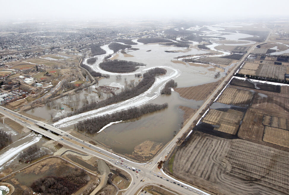 The ice covered Assiniboine River that has flooded its banks into surrounding fields and parks is seen west of the intersection of 18th St. and Grand Valley Rd. (bottom section) on Friday. The flooding has extended to Grand Valley Rd. at 18th St. but would still have to rise quite a bit to flood the road.