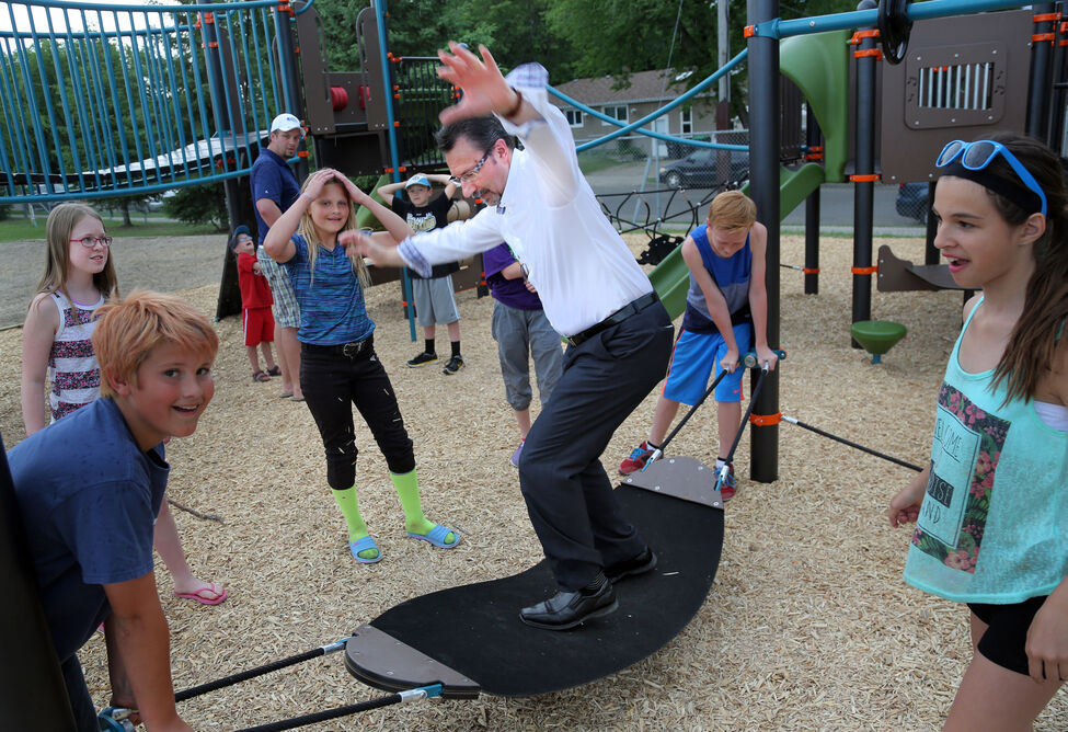 Mayor Rick Chrest tries his hand at the new playground structure at Valleyview School in June. The school opened the structure after fundraising by parents contributed $100,000 since 2011.