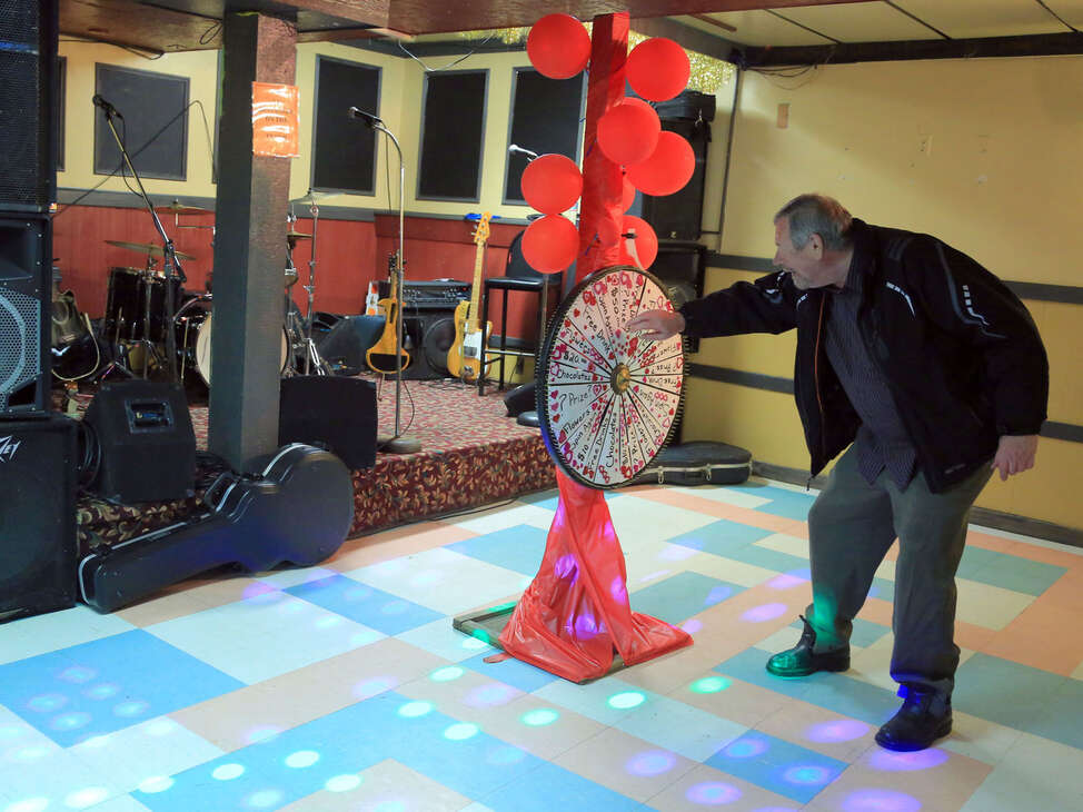 A patron tries his luck on a prize wheel set up for Valentine's Day.