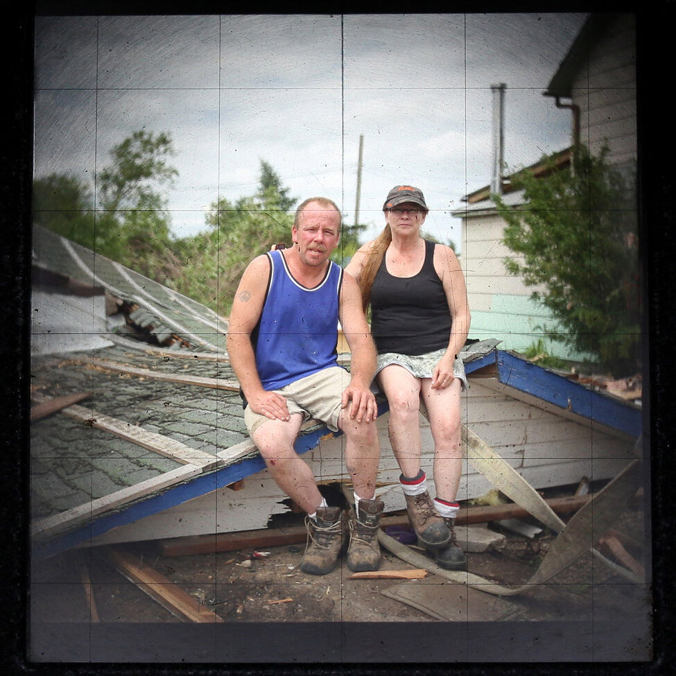 Shawn Wallace and Lee Jackson sits atop the roof of what was their garage outside their home before removing it with the help of members of Souris River Hutterite Colony. When the storm blew in their front door, Lee fought hard against the wind to force it back closed.