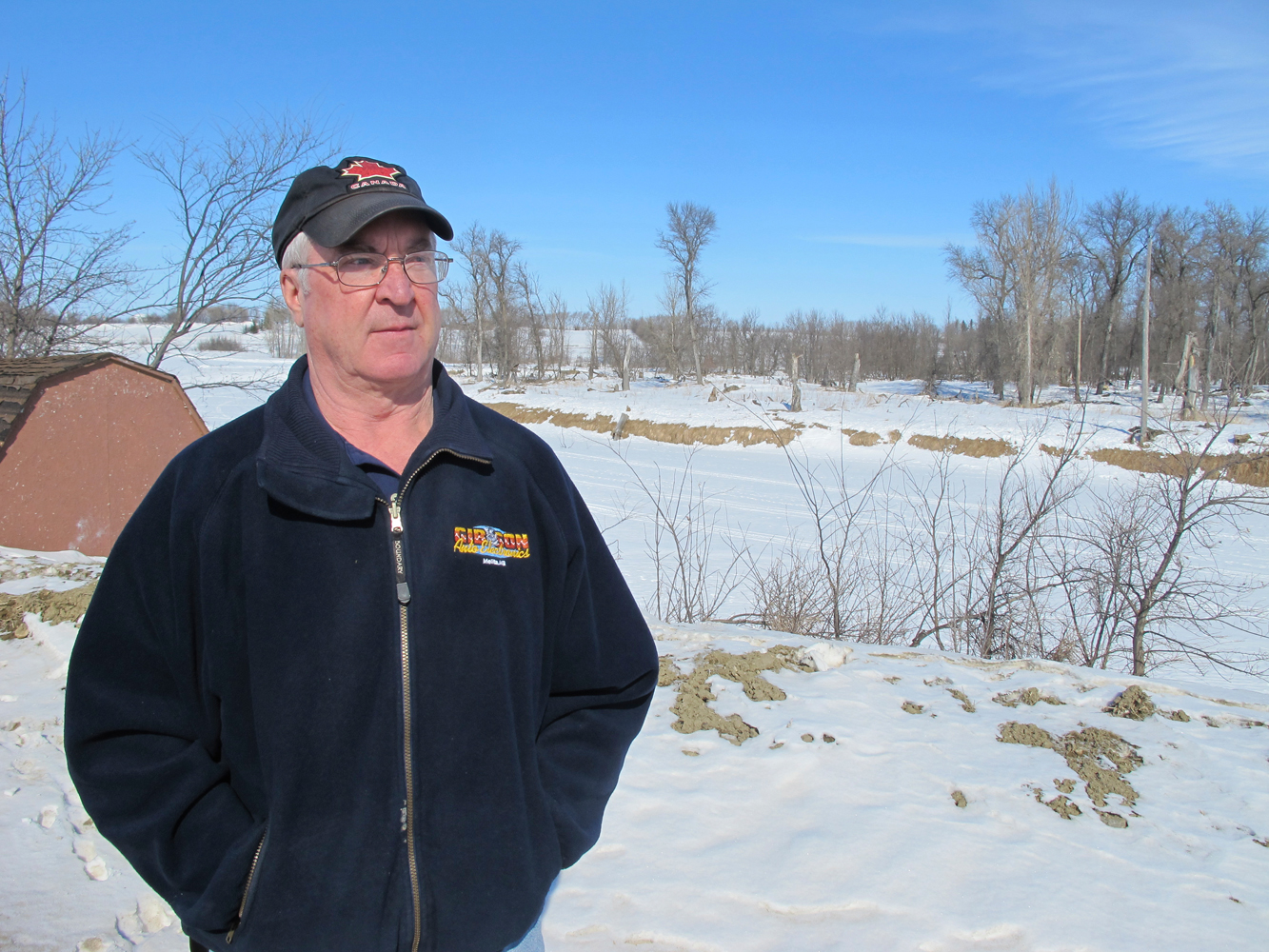 In early March, Melita Mayor Bob Walker stands on a dike raised by the province in 2009 at a cost of $500,000, with the Souris River in the background. He expects his town to be safe but said he's never seen the river this high at this time of year.  (Bartley Kives / Winnipeg Free Press)