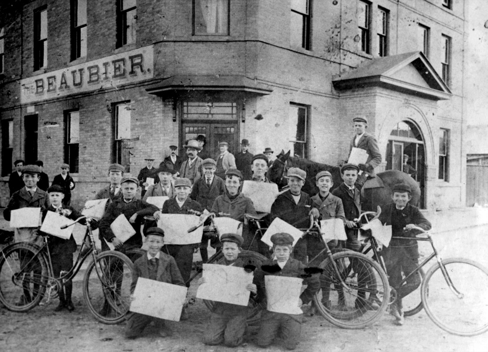 A group of newspaper carriers — including boys on bicycles and one on a horse —gather for a photo outside the Beaubier Hotel in downtown Brandon, circa the 1920s.