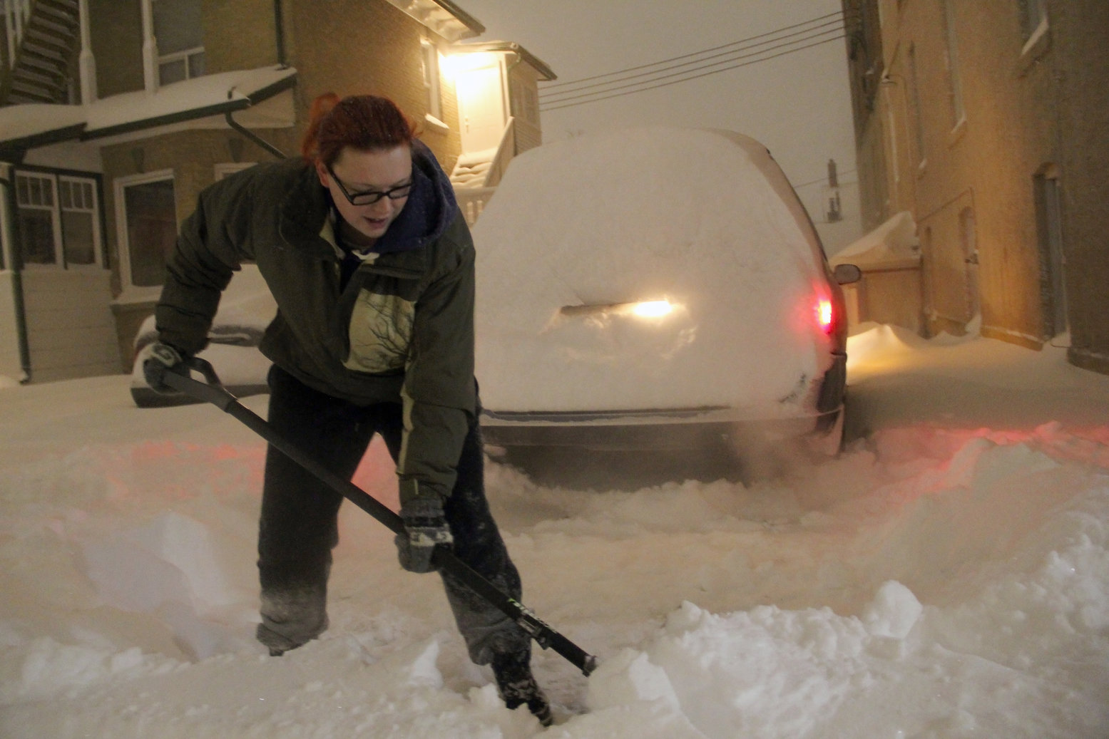 Kylie Black, 24, clears a path so her sister can get to work early Monday morning off of Lorne Avenue in Brandon. (Ian Froese/The Brandon Sun)