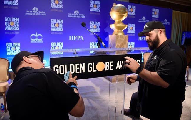 John Langhammer, left, and Brian Cooper, of Crews Unlimited II, set up the podium prior to the announcements of the nominations for the 76th Annual Golden Globe Awards at the Beverly Hilton hotel on Thursday, Dec. 6, 2018, in Beverly Hills, Calif. The 76th annual Golden Globe Awards will be held on Sunday, Jan. 6, 2019. (Photo by Chris Pizzello/Invision/AP).