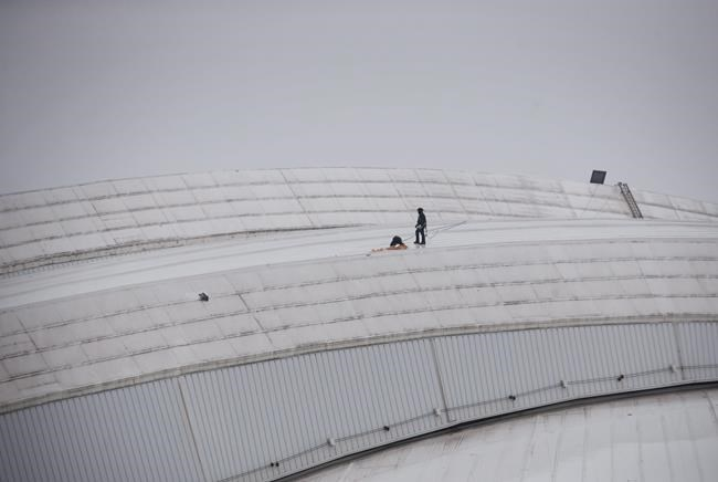 Workers examine a hole in top of the Rogers Centre as the area around the CN Tower is closed off due to reports of falling ice in Toronto on Monday, April 16, 2018. THE CANADIAN PRESS/Cole Burston