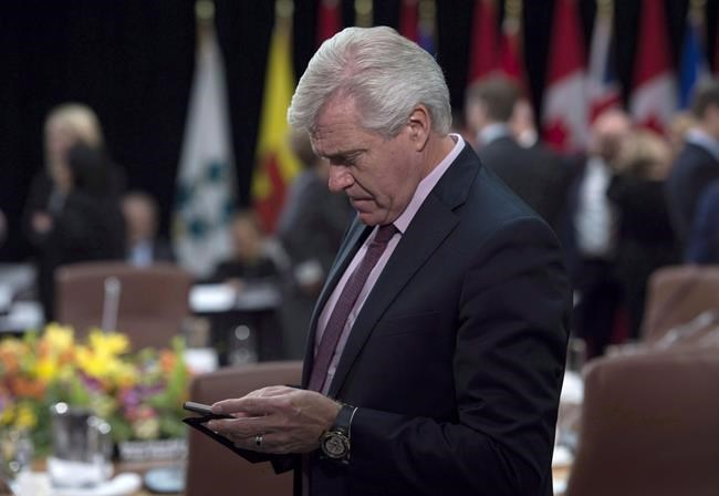 Newfoundland and Labrador Premier Dwight Ball checks his mobile device as he waits for the First Ministers Meeting to begin in Ottawa, Tuesday, October 3, 2017. Lawyers for Ball are expected to make arguments in Supreme Court today over a publication ban on documents in the murder trial of a man who used to date his daughter. THE CANADIAN PRESS/Adrian Wyld