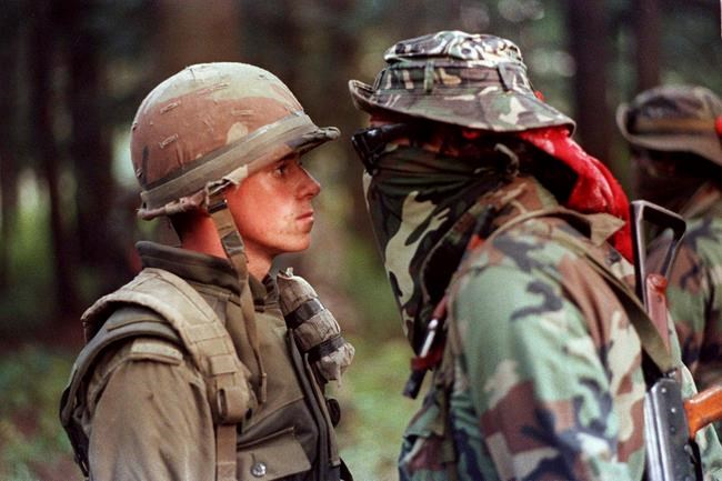 """Canadian soldier Patrick Cloutier and Saskatchewan Native Brad Laroque alias """"Freddy Kruger"""" come face to face in a tense standoff at the Kahnesatake reserve in Oka, Que., Saturday, Sept. 1, 1990. THE CANADIAN PRESS/Shaney Komulainen"""