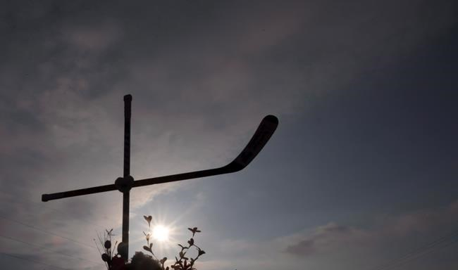 A cross made out of hockey sticks at a makeshift memorial is silhouetted against the setting sun at the intersection of a fatal bus crash near Tisdale, Sask. on Monday, April, 9, 2018. THE CANADIAN PRESS/Jonathan Hayward