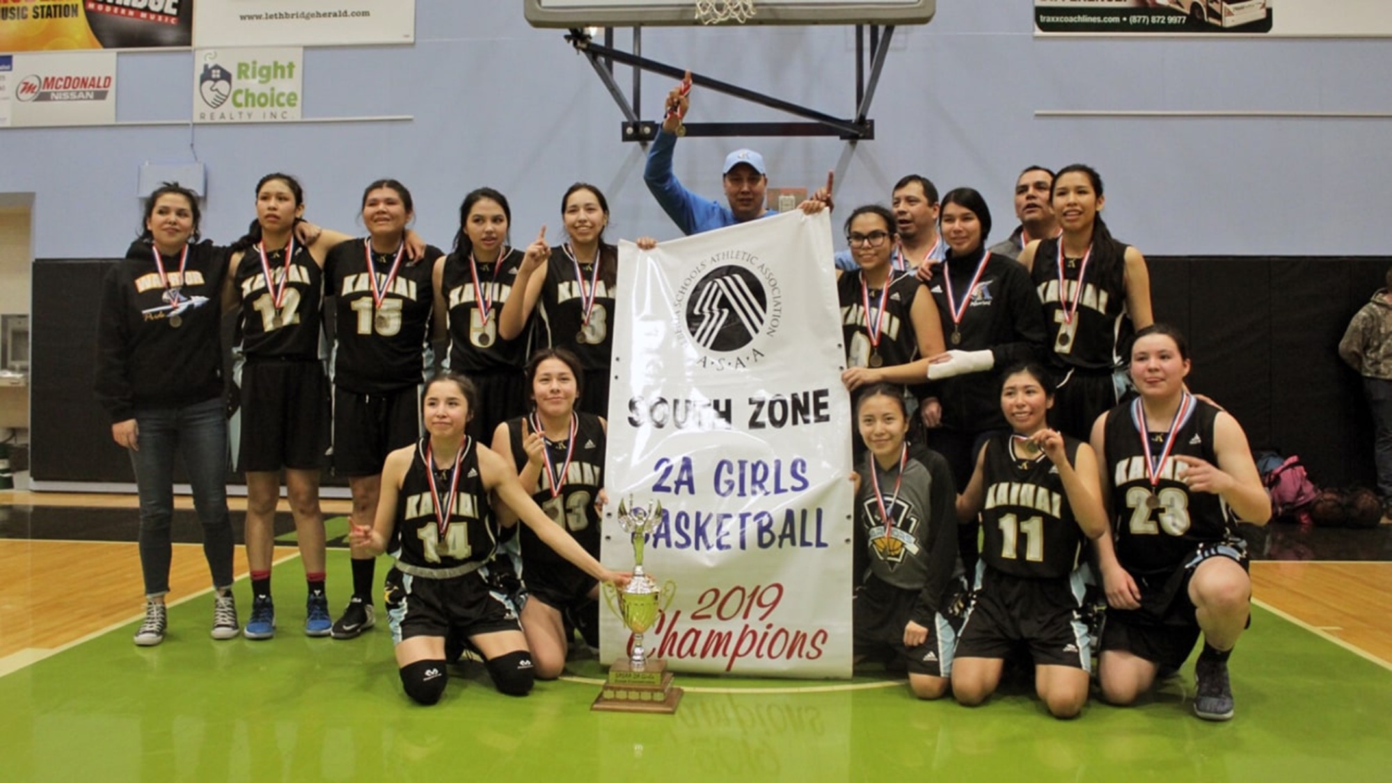 Charlton Weasel Head, back middle, and his Kainai Warriors senior girls' basketball team celebrate their 2A south zone title.