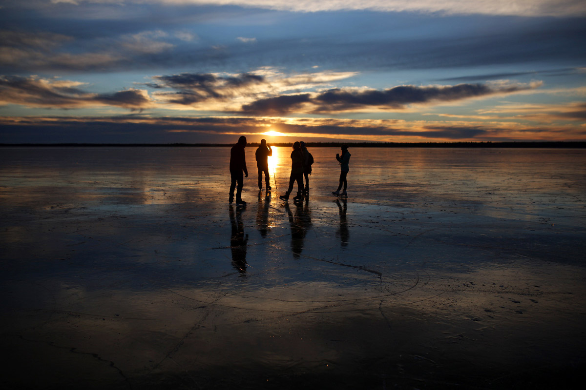 Ice skaters chat on the smooth-as-glass ice covering Clear Lake as the sun sets in Riding Mountain National Park on a sunny and warm Monday afternoon. The lack of snow so far this year has created a rare opportunity for winter enthusiasts to enjoy the clear ice. In some areas you can see straight through to the bottom of the lake. (Tim Smith / Brandon Sun)