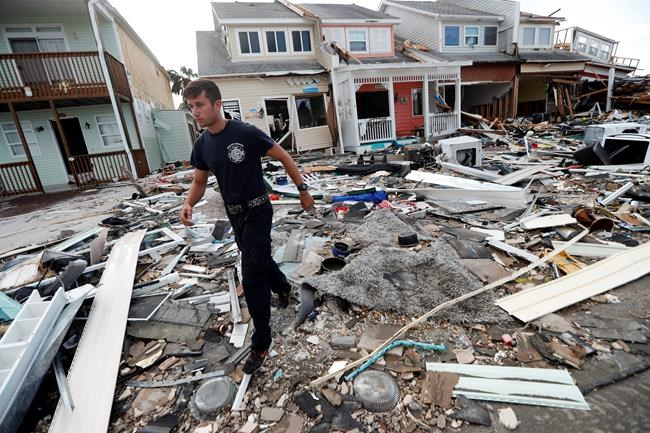 Firefighter Austin Schlarb performs a door to door search in the aftermath of Hurricane Michael in Mexico Beach, Fla., Thursday, Oct. 11, 2018. (AP Photo/Gerald Herbert)