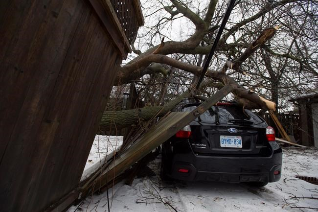 A car damaged by a fallen tree branch is shown in Toronto, Monday, April 16, 2018. Tens of thousands of people across southern and central Ontario remained without power Monday morning as the province's massive ice storm transitioned to drenching rain. THE CANADIAN PRESS/Frank Gunn