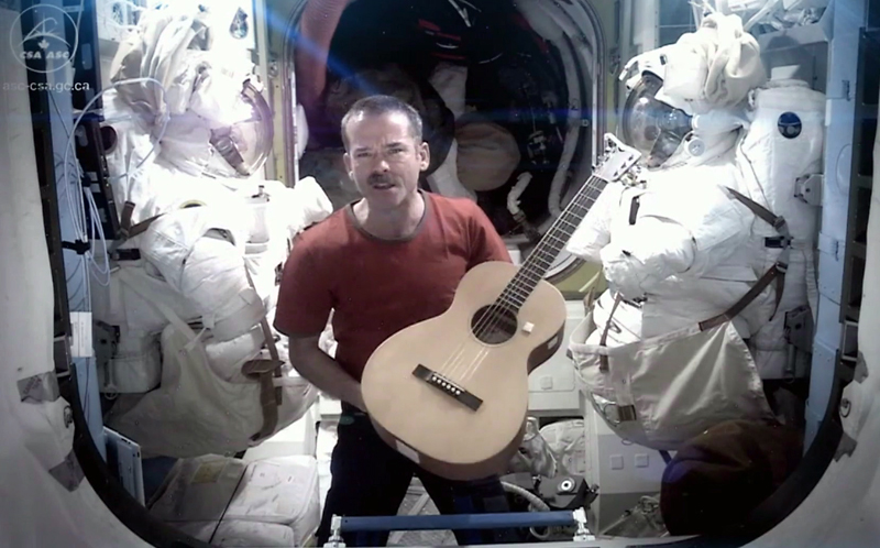 """Canadian astronaut and ISS commander Chris Hadfield is framed by spacesuits as he performs David Bowie's """"Space Oddity"""" during his stint last year as commander of the International Space Station. This Monday, he will again be front and centre in the music world when the song I.S.S (""""Is Somebody Singing""""), which Hatfield co-wrote with Ed Robertson of the Barenaked Ladies, is broadcast countrywide during Music Monday celebrations."""