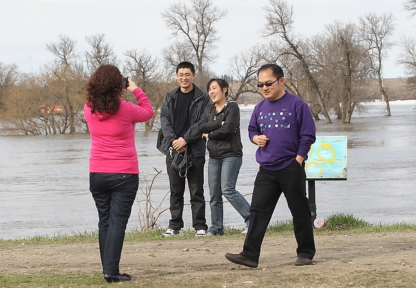 08052011Despite warnings to stay off the dikes flood watchers take photos of the Assiniboine River from the dike near Assiniboine Ave. in Brandon on Sunday evening.   (Tim Smith/Brandon Sun) (Tim Smith/Brandon Sun)