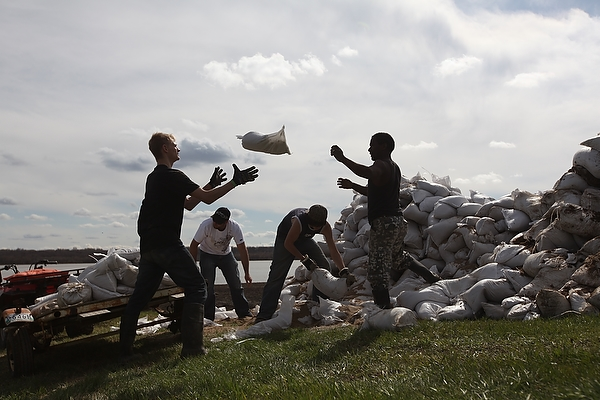 07052011Volunteers are silhouetted as they load sandbags onto a trailer while building a sandbag dike around a home on the south side of Grand Valley Road in the RM of Whitehead on Saturday. Dozens of volunteers came and went throughout the day to help protect the homes from the rising Assiniboine River. (Tim Smith/Brandon Sun) (Tim Smith/Brandon Sun)