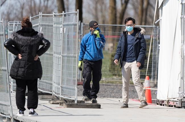 People are seen at a COVID-19 testing clinic in Montreal North, Saturday, May 2, 2020, as the COVID-19 pandemic continues in Canada and around the world. THE CANADIAN PRESS/Graham Hughes