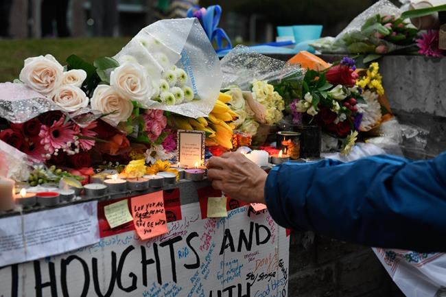 A man lights a candle at a vigil on Yonge Street in Toronto, Tuesday, April 24, 2018. Ten people were killed and 14 were injured in Monday's deadly attack in which a van struck pedestrians in northern Toronto. THE CANADIAN PRESS/Galit Rodan