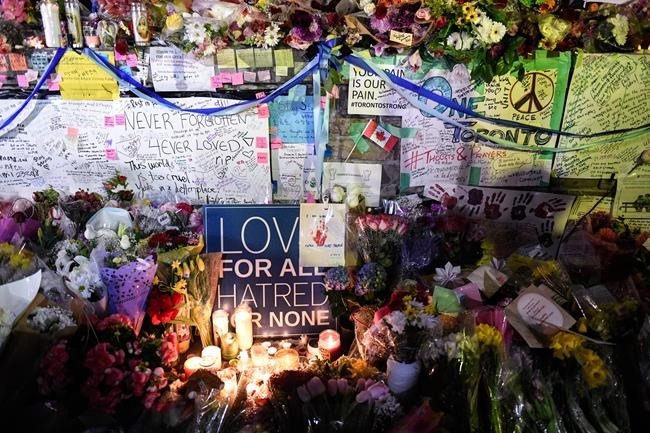 Flowers, notes and candles are piled high at a vigil on Yonge Street in Toronto, Tuesday, April 24, 2018. Ten people were killed and 14 were injured in Monday's deadly attack in which a van struck pedestrians in northern Toronto. THE CANADIAN PRESS/Galit Rodan