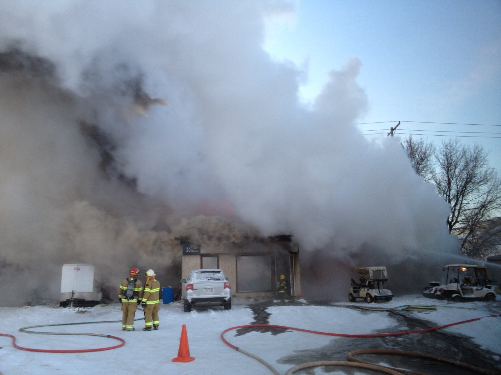 Firefighters pour water on a Pacific Avenue fire near Second Street on Monday morning.