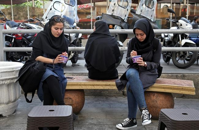 Iranian women eat ice-cream on a sidewalk in downtown Tehran, Iran, Monday, May 7, 2018. Iranian President Hassan Rouhani has seen his influence wane as his signature achievement, the nuclear deal with world powers, is now under threat from President Donald Trump. Economic problems, as well as some suggesting a military dictatorship for the country, suggest Iran's domestic politics may swing back toward hard-liners and further weaken the once-popular president. (AP Photo/Vahid Salemi)