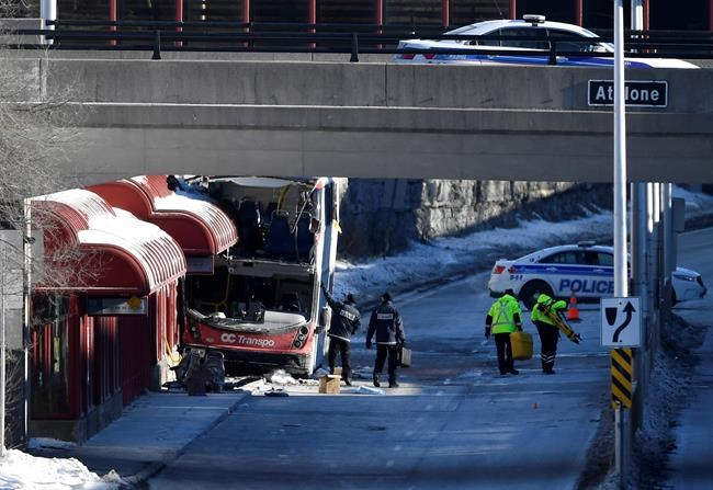 Officials from Transport Canada look at the scene where a double-decker city bus struck a transit shelter at the start of the afternoon rush hour on Friday, at Westboro Station in Ottawa, on Saturday, Jan. 12, 2019. THE CANADIAN PRESS/Justin Tang