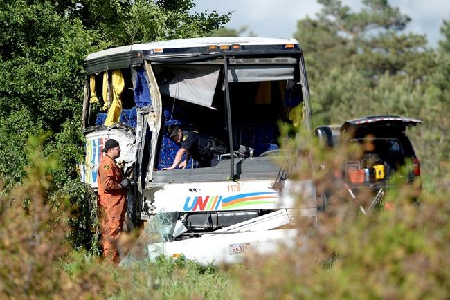 OPP officers work at the site of a crash involving a tour bus on Highway 401 West, near Prescott, Ont. on Monday, June 4, 2018. At least 24 people are in hospital, four with life-threatening injuries, after a bus crash in eastern Ontario, provincial police said Monday. THE CANADIAN PRESS/Justin Tang