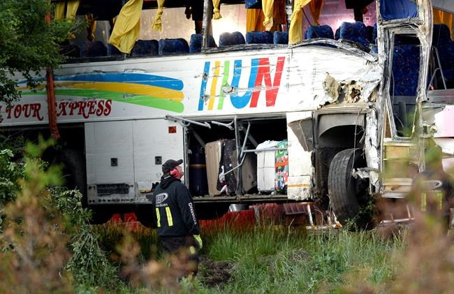 A tow operator looks towards the damaged side of a tour bus that was involved in a crash on Highway 401 West, near Prescott, Ont. on Monday, June 4, 2018. THE CANADIAN PRESS/Justin Tang