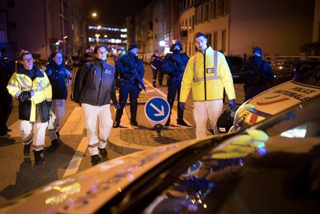 Rescue workers walk past hooded police officers in Strasbourg, eastern France, Thursday Dec. 13, 2018. A top French official says a man has been killed in a shootout with police in Strasbourg, but he has not been confirmed as the suspected gunman who killed three people near a Christmas market. (AP Photo/Jean-Francois Badias)