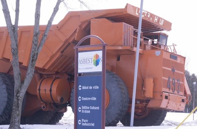 The town sign is seen in from of a mining truck in Asbestos, Que. on Wednesday, March 11, 2020. he town of Asbestos, Que., looking to shed its link to mining town past for a new name has narrowed it down to four possible options. THE CANADIAN PRESS/Paul Chiasson