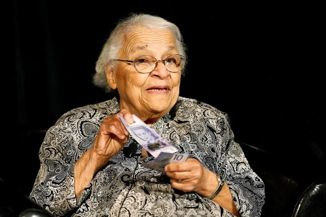 Clutching some $10 banknotes Wanda Robson, Viola Desmond's sister, the first Canadian woman on a banknote, shows her sister's portrait on Canada's new $10 banknote at the Canadian Museum For Human Rights in Winnipeg, Monday, Nov. 19, 2018. Bank of Canada Governor Stephen Poloz and Robson, officially launched the unique, vertically oriented purple bill. THE CANADIAN PRESS/John Woods