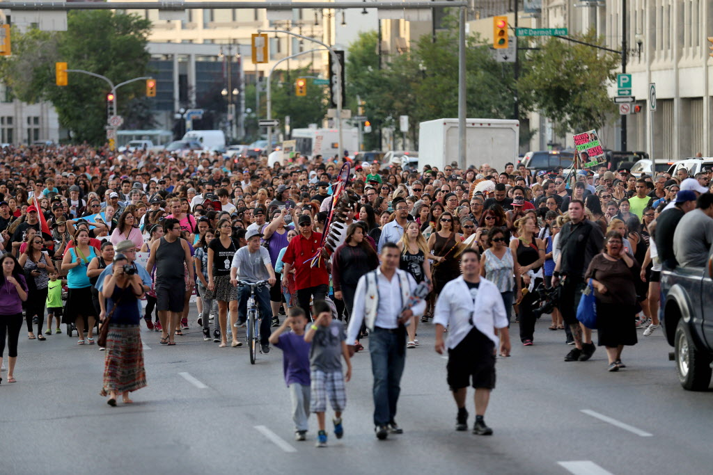 People walk along Main Street from the Alexander Docks to the Oodena Circle at The Forks during a vigil for Tina Fontaine and Faron Hall. (Trevor Hagan / The Canadian Press )