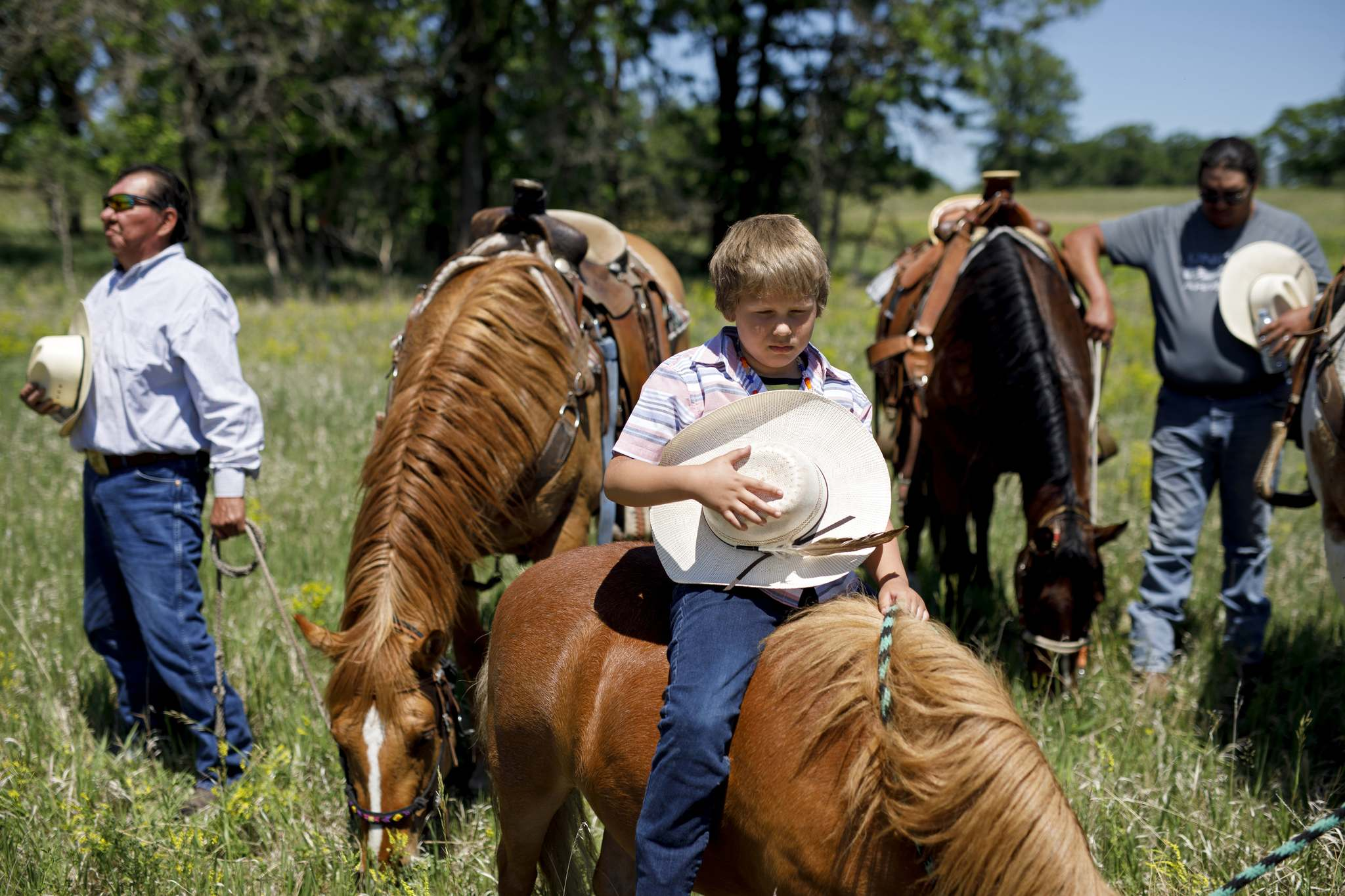 Seven-year-old Jase Tacan holds his hat to his chest atop his miniature horse Charlie while drummers perform at the former Brandon Indian Residential School site on Monday. Dakota Nation Unity Riders from Sioux Valley Dakota Nation and support riders rode to the school site from the Grand Valley Campground in honour of residential school victims and survivors. A ceremony was also held at the former school site, now owned by Sioux Valley Dakota Nation, where survivors from the First Nation attended. Please see Page A4 for more photos. (Tim Smith/The Brandon Sun)</p></p>